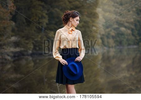 outdoor fashion portrait of sensual stylish girl in vintage clothes with lake and forest on the background. Young woman with romantic hairstyle and floppy hat walks in the forest. Female retro look