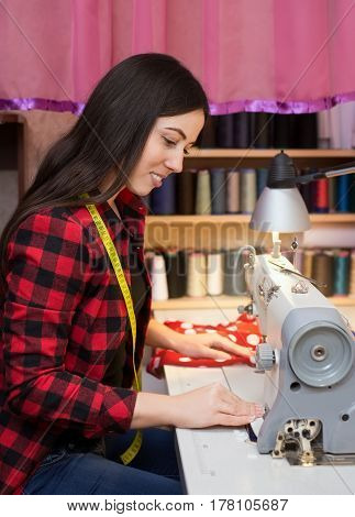 portrait of young woman seamstress sitting and sews on sewing machine. Dressmaker work on the sewing machine. Tailor making a garment in her workplace