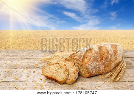 sliced loaf with dry ears of wheat on wooden table with golden field on the background. Fresh baked traditional bread on nature background. Ripe cereal field, blue sky with beautiful clouds and sun