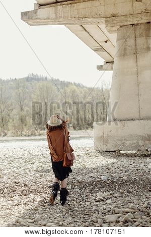 Stylish Boho Woman Posing At River, Back View. Beautiful Gypsy Girl With Hat And Fringe Poncho And B