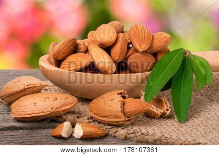 heap of peeled almonds with leaf on a wooden table with blurred garden background.