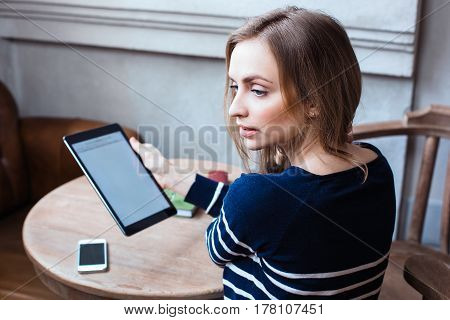 Young female student is enjoying free timewhile is sitting with touch pad in coffee shop indoor. Beautiful woman is holding digital tablet and consider for someone during rest in cafe