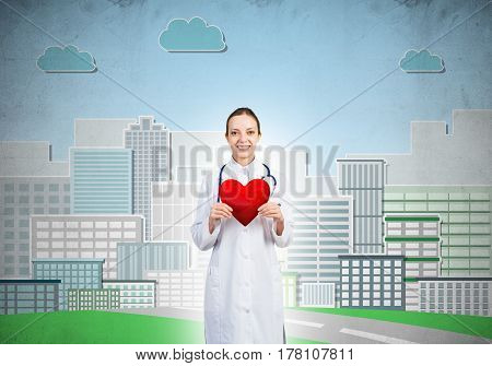 Young woman doctor against illustration background holding red heart