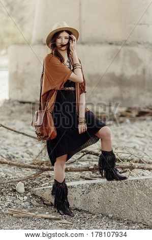 Beautiful Stylish Boho Woman With Hat, Leather Bag, Fringe Poncho And Boots. Girl In Gypsy Hippie Lo