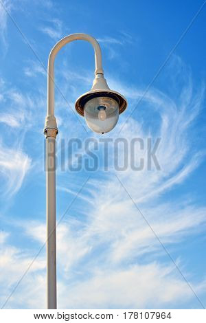 Lamppost on the seafront on the shore of clouds