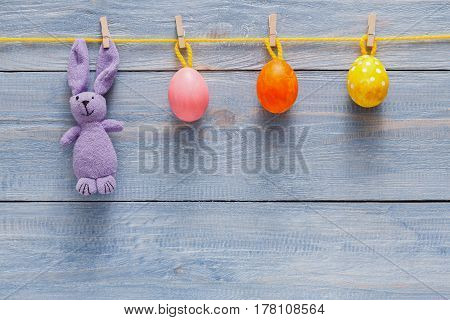 Handmade easter garland with painted eggs and bunny on wood background. Colorful holiday decoration on rustic table top view