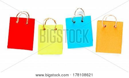 Row of four shopping bags of colorful paper with rope handles. Isolated over white background