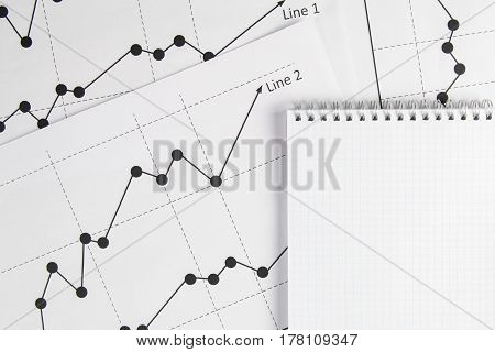 Business drawing chart graphics and white notepad