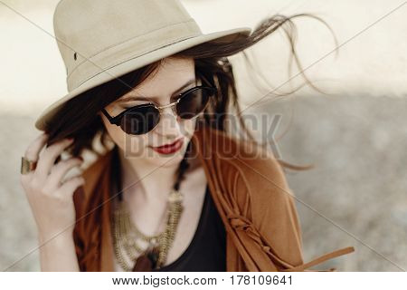 Stylish Boho Woman In Sunglasses Holding Hat, With Windy Hair. Hipster Girl In Gypsy Look, Young Tra