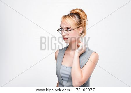 Young nice woman concentrated on complicated issues, problems, personal troubles. Inability to solve the situation, mistrust, anxiety. Grey background with free space.