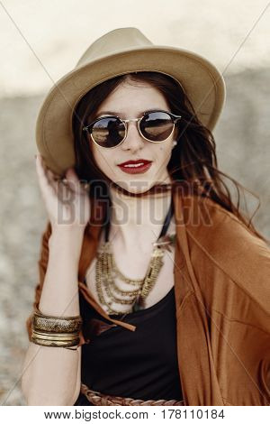 Beautiful Stylish Hipster Woman Portrait In Sunglasses Holding Hat, With Windy Hair. Boho Traveler G