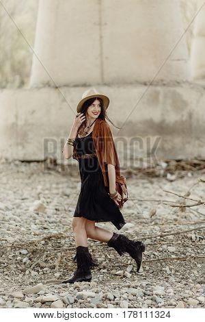 Stylish Boho Woman With Hat, Leather Bag, Fringe Poncho And Boots Walking Near River Under Bridge St
