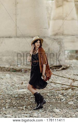 Beautiful Stylish Hipster Woman Walking With Hat, Leather Bag, Fringe Poncho And Boots. Boho Travele