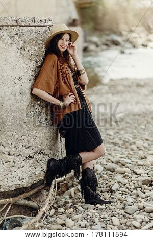 Stylish Hipster Woman In Hat And Fringe Poncho Posing. Boho Traveler Girl In Gypsy Look, Near Beach