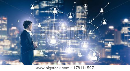 Thoughtful businessman against night cityscape working with social connection media concept