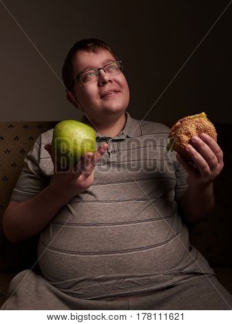 Man with big belly thinking of what to eat - apple or burger.