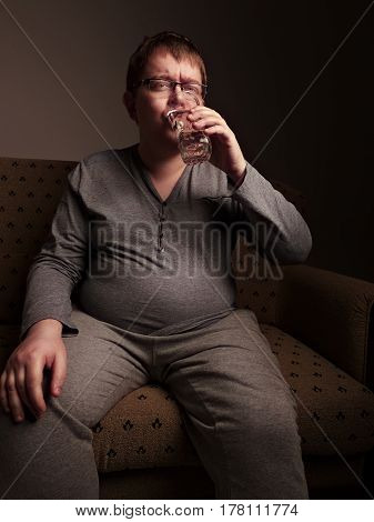 Overweight man drinking water while. Studio shot.