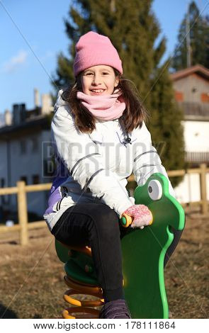 pretty little girl playing on the little carousel of a playground in winter