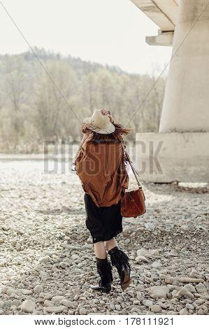 Stylish Boho Woman Walking At River Under Stone Bridge, Back View. Beautiful Gypsy Girl With Hat And