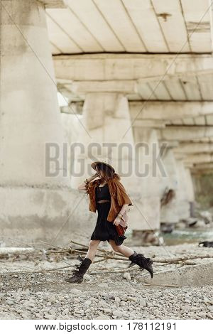 Beautiful Stylish Hipster Woman Jumping, Having Fun In Hat, Leather Bag, Fringe Poncho And Boots. Bo