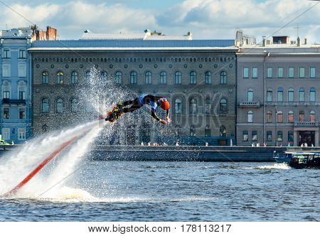 Athlete flybarless dives into the water on the Neva river on the background of the waterfront, buildings and blue sky. St. Petersburg, summer, 2015