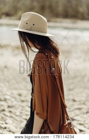 Stylish Hipster Woman In Hat, Fringe Poncho Walking On River Beach. Boho Traveler Girl In Gypsy Look