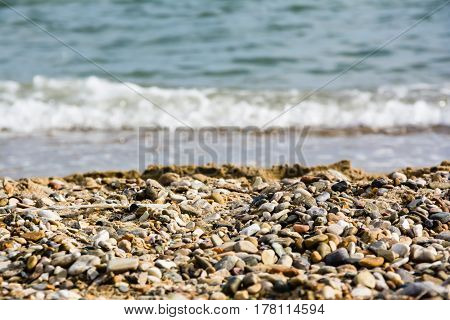 Brown Pebble (small Stones) In The Foreground With Blurred Sea Tidal Waves And The Horizon Line In T