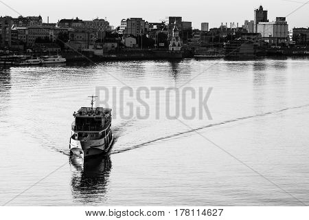 Ship sailing in water at sunset with city in the background toned black and white