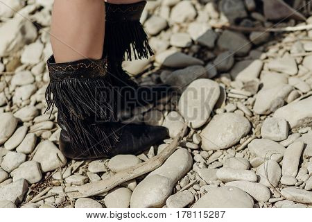 Fringe Boot. Stylish Hipster Boho Traveler Woman Wearing Suede Boots On River Beach. Gypsy Girl Look