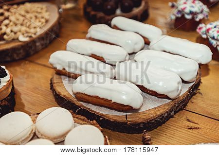 Eclairs traditional french dessert. Yellow wooden table candybar
