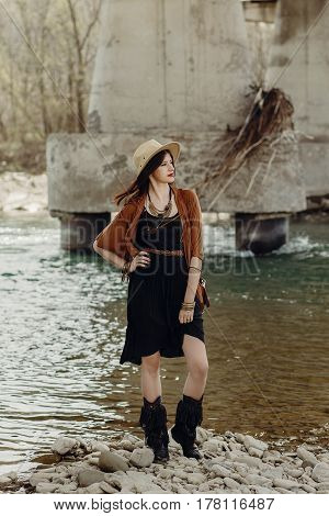 Stylish Boho Woman With Jewelry Posing At River. Beautiful Gypsy Dressed Girl With Hat And Fringe Po