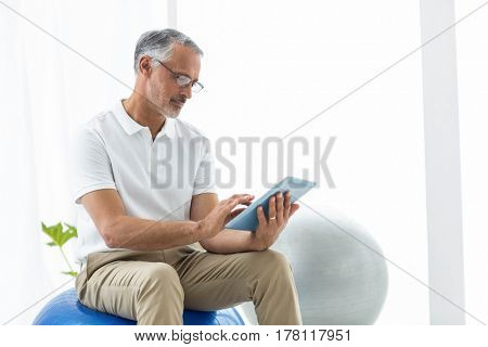 Physiotherapist sitting in exercise ball and using digital tablet at home