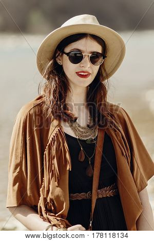 Stylish Hipster Boho Woman In Sunglasses With Hat, Leather Bag, Fringe Poncho And Accessory. Travele