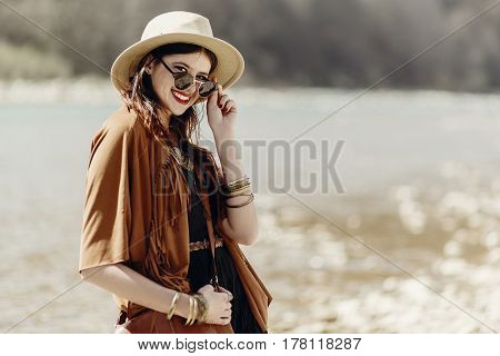 Stylish Hipster Boho Woman Smiling In Sunglasses With Hat, Leather Bag, Fringe Poncho And Accessory.