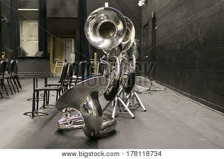 tubas resting at the back of the stage