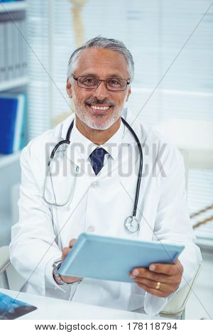 Portrait of smiling doctor using digital tablet at clinic