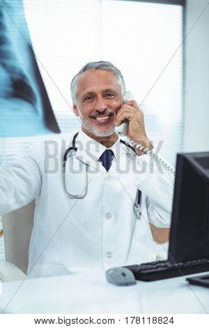 Portrait of doctor checking a x-ray report while talking on phone at clinic