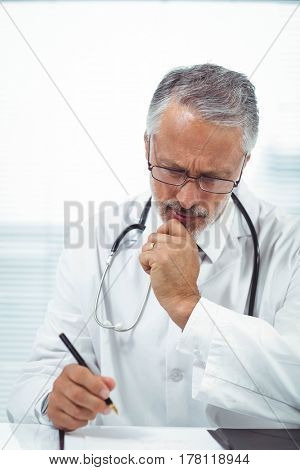 Doctor writing on notepad at clinic