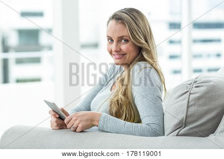 Portrait of pregnant woman sitting on sofa and using smartphone