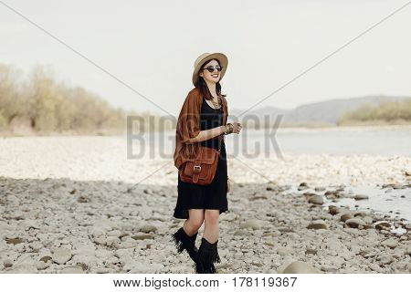 Happy Stylish Hipster Traveler Woman In Hat, Fringe Poncho Walking Near Water River Beach In Mountai