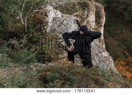 The Assassin Ninja Sword Crouched On Cliff Rocks In Ambush