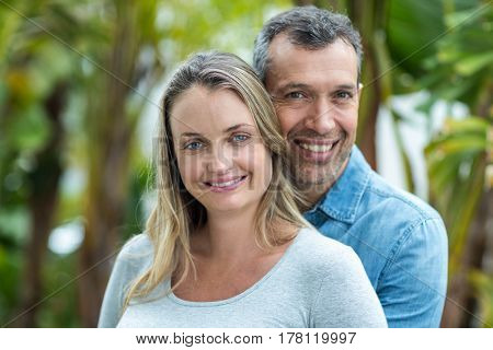 Couple looking at camera and smiling outdoors