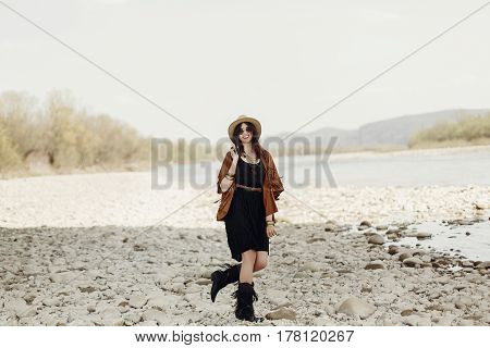 Stylish Boho Traveler Woman In Hat, Fringe Poncho Walking Near Water River Beach In Mountains, Gypsy