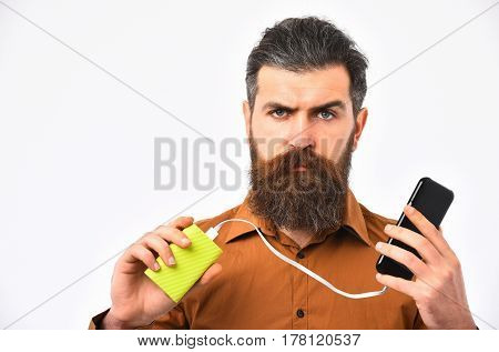 bearded man long beard brutal caucasian hipster with moustache charging mobile or cell phone with green power bank battery has serious face in orange color shirt isolated on white background