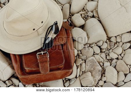 Stylish Hipster Hat And Sunglasses And Leather Bag On Beach With Space For Text, Top View. Wanderlus