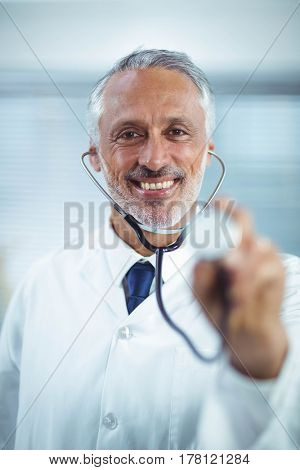 Happy doctor holding stethoscope in clinic
