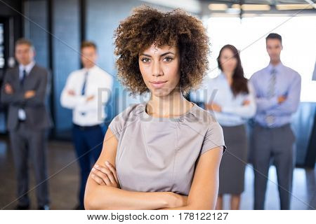 Successful businesswoman smiling at camera while her colleagues standing behind him in office
