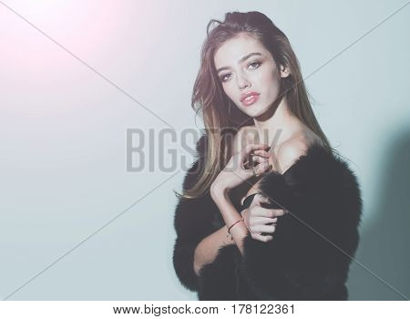 young pretty woman or cute sexy girl with long beautiful curly blonde hair and adorable face in black fur vest or waistcoat on grey background copy space