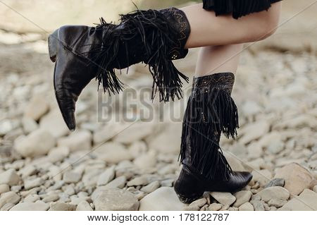 Boho Girl Walking In Fringe Boot. Stylish Hipster Traveler Woman Wearing Suede Boots On River Beach.