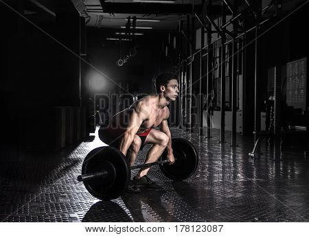 Muscular shirtless man lifting a barbell in crossfit gym. oncentrating to deadlift a barbell.